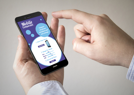Close up of man using 3d generated mobile smart phone with mobile rates and plans comparator on the screen. Screen graphics are made up. Stock Photo