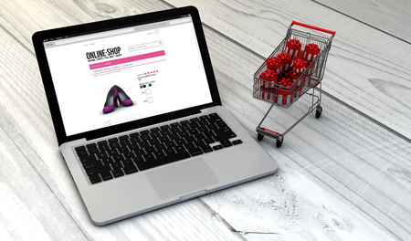 merchandise: e-commerce concept: Digital generated laptop with shopping cart full of christmas or gift boxes over wooden desk with online shop. All screen graphics are made up.