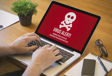 internet security: Businessman at work. Close-up top view of man working on laptop virus infected. all screen graphics are made up. Stock Photo