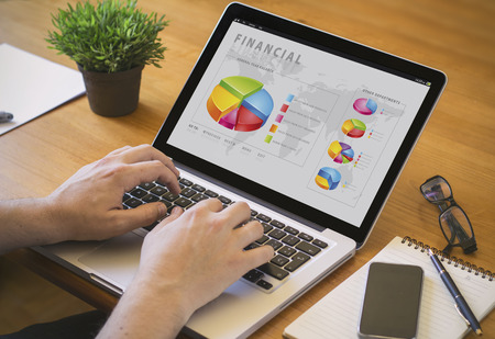 Online Business: Businessman at work. Close-up top view of man working on laptop with finances software. all screen graphics are made up.