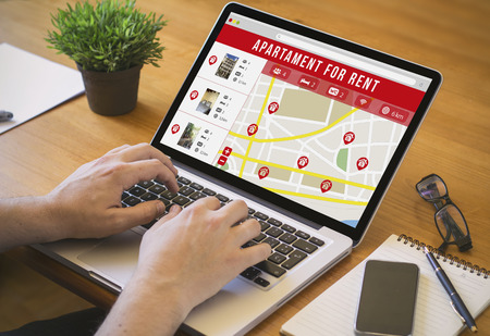 Businessman at work. Close-up top view of man working on laptop apartment search website. All screen graphics are made up. No real player names.