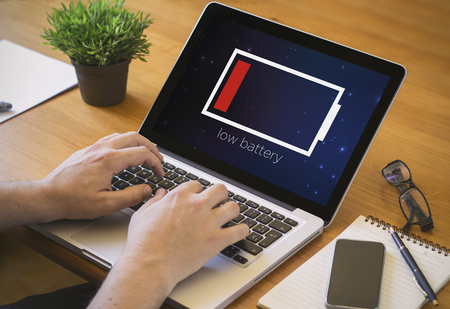 Businessman at work. Close-up top view of man working on laptop with low battery. all screen graphics are made up.