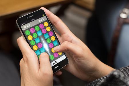 Concepto de entretenimiento: chica usando un teléfono digital generada con el videojuego en la pantalla. Todos los gráficos de la pantalla se componen. Foto de archivo - 46461439