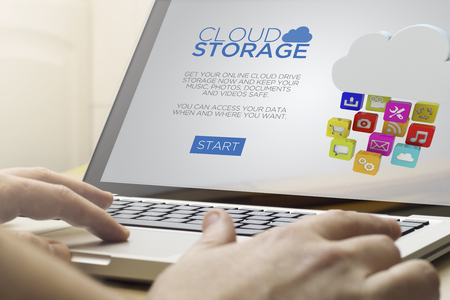 safe and sound: cloud information concept: man using a laptop with digital drive storage website on the screen. Screen graphics are made up. Stock Photo