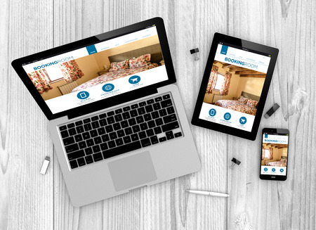 Digital generated devices over a wooden table. laptop, tablet and white smartphone with made up responsive booking website . Stock Photo