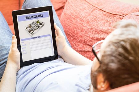 household insurance: technology lifestyle concept: hipster on the sofa with home insurance tablet.