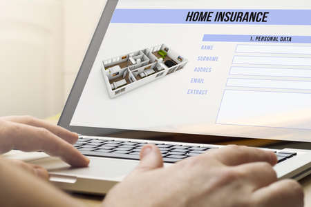 household insurance: house protection concept: man using a laptop with home insurance on the screen. Stock Photo