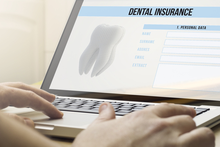 dental insurance: health protection concept: man using a laptop with dental insurance on the screen.