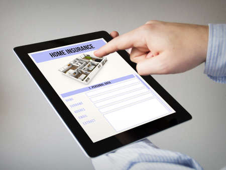 household insurance: new technologies concept: hands with touchscreen tablet with home insurance on the screen.