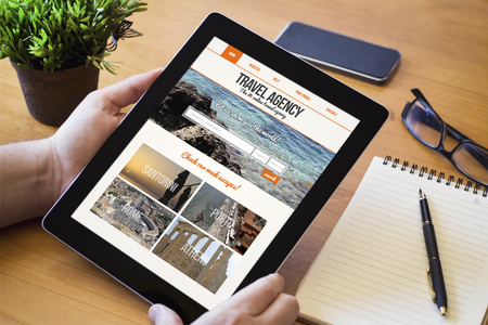 reiseb�ro: hands of a man holding a travel agency website on screen device over a wooden workspace table. All screen graphics are made up. Lizenzfreie Bilder