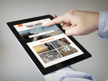 new technologies: new technologies concept: hands with touchscreen tablet with travel agency website on screen. Screen graphics are made up.
