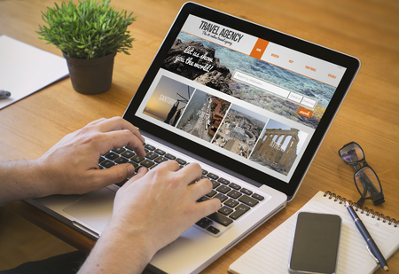 Businessman at work. Close-up top view of man working on laptop withtravel agency website on screene. all screen graphics are made up.