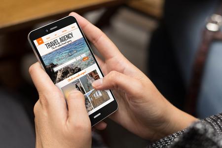 agencia de viajes: el concepto de viaje: chica usando un teléfono digital generada con el sitio web de la agencia de viajes en la pantalla. Todos los gráficos de la pantalla se componen.