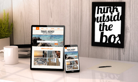 Digital generated tablet and phone on a desktop workplace travel agency website on screen. All graphics are made up. Stock Photo