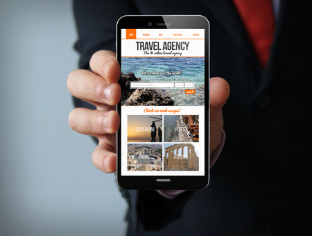 corporate travel: new technologies travel concept: businessman hand holding a 3d generated touch phone with travel agency website on screen. Screen graphics are made up. Stock Photo