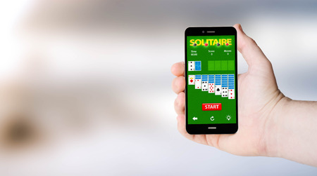 games hand: mobile phone with soliaire app on digital generated phone screen with sea background.