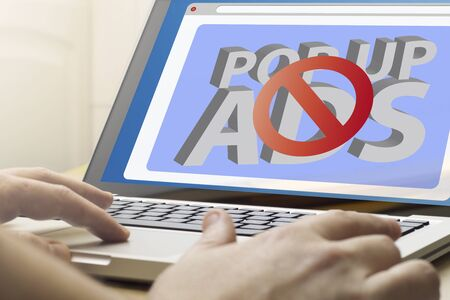 ad: online advertising concept: man using a laptop with ads blocker on the screen.