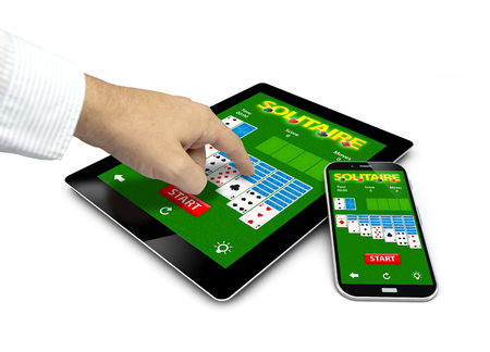 ace of spades: group of touchscreen devices with solitaire app and a hand touching the screen isolated on white background.