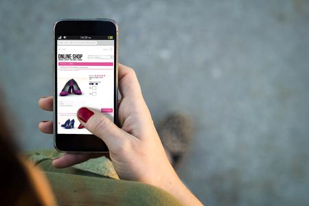 Draufsicht der Frau zu Fuß in der Straße ihr Handy mit Online-Shop auf dem Bildschirm mit Exemplar verwenden.