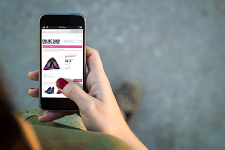 orden de compra: Vista superior de la mujer que camina en la calle utilizando su teléfono móvil con la tienda en línea en la pantalla con el copyspace.