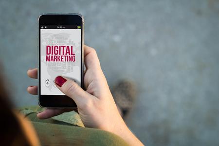 esquema: Vista superior de la mujer que camina en la calle utilizando su tel�fono m�vil con el marketing digital en pantalla. Foto de archivo