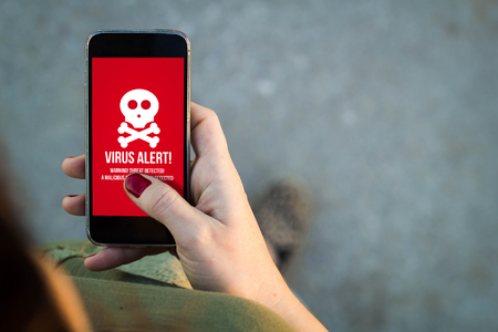 alert: Top view of woman walking in the street using her mobile phone with virus alert in the screen with copyspace. Stock Photo