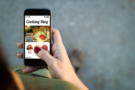 Top view of woman walking in the street using her mobile phone with cooking blog on screen. Stock Photo