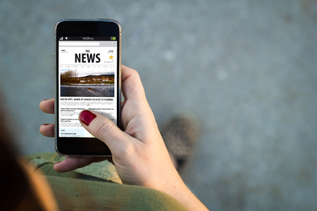articles: Top view of woman walking in the street using her mobile phone reading news in the screen with copyspace.