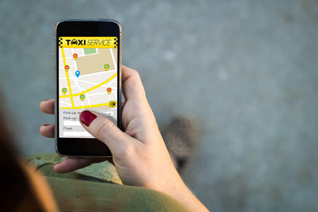 taxi sign: Top view of woman walking in the street using her mobile phone with taxi service in the screen with copyspace. Stock Photo