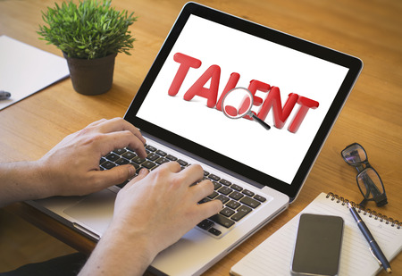 cool man: talent search online concept. Close-up top view of a coolhunter working on laptop. Stock Photo