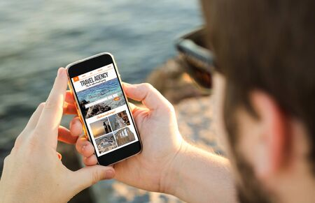best travel destinations: man on the coast using his smartphone to travel online. All screen graphics are made up.