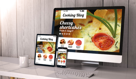 Digital generated devices on desktop, responsive blank mock-up with cooking blog website  on screen. All screen graphics are made up. Stock Photo