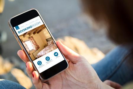 close-up van de jonge vrouw die een smartphone met boeken kamer app op het scherm. Alle screen graphics zijn opgebouwd. Stockfoto
