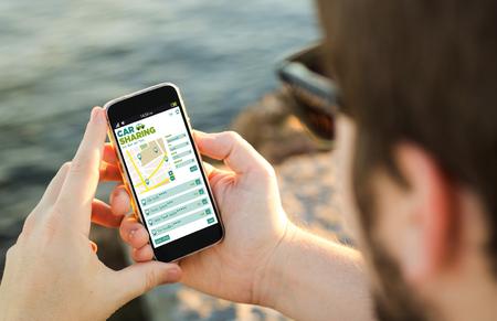 El hombre en la costa con el coche compartido de aplicaciones en su teléfono inteligente. Todos los gráficos de la pantalla se componen. Foto de archivo - 49256729