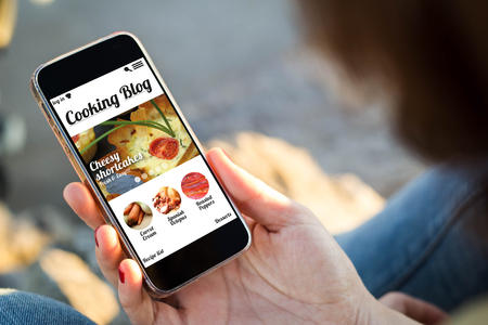 close-up view of young woman holding a smartphone with cooking blog on screen. All screen graphics are made up.