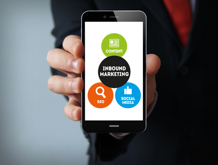 inbound: Business concept: businessman hand holding a touch phone with Inbound Marketing on the screen Stock Photo