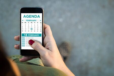 Top view of woman walking in the street using her mobile phone to check agenda. All screen graphics are made up.