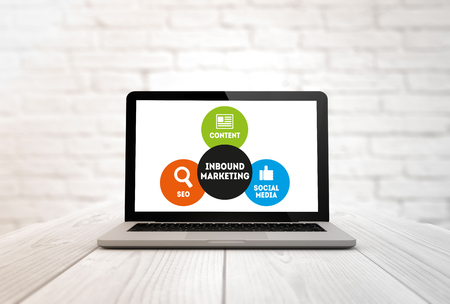 inbound marketing: digitally generated laptop on a wooden table with Inbound Marketing. Screen graphics are made up. Stock Photo