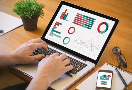 eficiencia: BYOD concepto: el ordenador portátil y smartphonep en un lugar de trabajo de escritorio. Todos los gráficos de la pantalla se componen.
