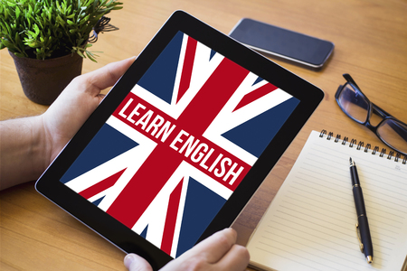 learn english: hands of a man holding a learn english device over a wooden workspace table. All screen graphics are made up.