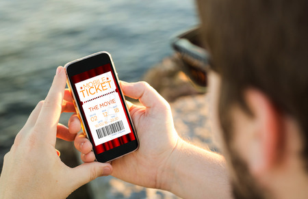 movie ticket: man on the coast using his smartphone to buy cinema tickets. All screen graphics are made up.