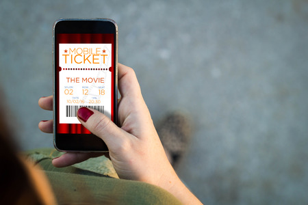 lady on phone: Top view of woman walking in the street using her mobile phone with cinema e-tickets. All screen graphics are made up. Stock Photo