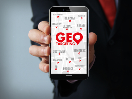 stationery needs: Business concept: businessman hand holding a touch phone with geo targeting on the screen Stock Photo