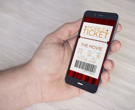 movie: hand with digital generated smartphone shopping cinema tickets. Screen graphics are made up. Stock Photo