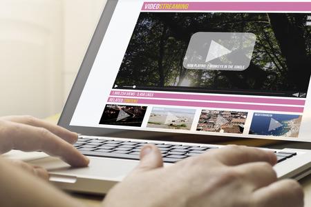 Online-Streaming-Konzept: Mann mit einem Laptop mit Online-Streaming-Website auf dem Bildschirm. Screen-Grafiken bestehen. Lizenzfreie Bilder