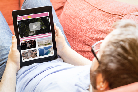 technology lifestyle concept: hipster on the sofa with video streaming tablet. Screen graphics are made up. Stock Photo