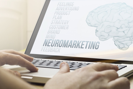 modern marketing concept concept: man using a laptop with neuromarketing on the screen. Screen graphics are made up.