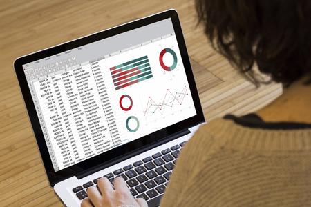 会計上の概念: ノート パソコンの画面上のスプレッドシート。画面のグラフィックが成っています。 写真素材