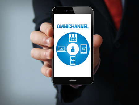 multi media: Business concept: businessman hand holding a touch phone with Omnichannel graphic on the screen Stock Photo