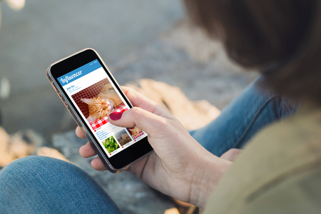 woman holding a smartphone and touching the screen with influencer website. All screen graphics are made up. Stock Photo